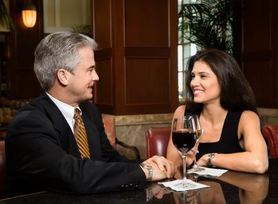 Couple sitting at bar talking.